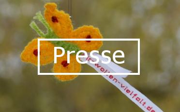 """Gelber Häkel-Schmetterling mit grünem Körper und Wäscheband mit Aufschrift """"wir-wollen-vielfalt.de"""". In der Mitte des Bildes steht das Wort """"Presse""""."""