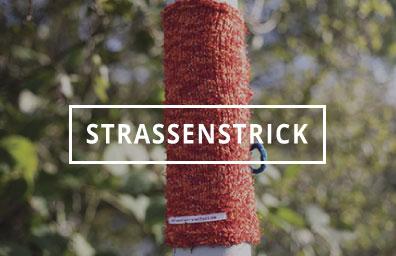 """Ein mit Strick dekorierter Laternenmast. Link zur Seite """"Straßenstrick""""."""