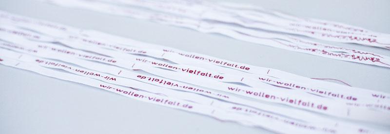 """Weiße Wäschebänder mit roter Aufschrift """"wir-wollen-vielfalt.de"""""""