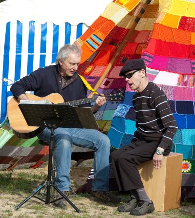 Ein Gitarrist und ein blinder Sänger sitzen vor dem Tipi
