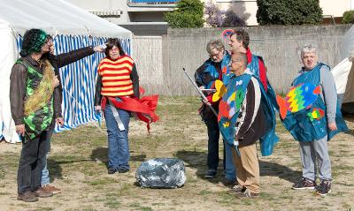 Menschen in Kostümen stehen um einen Stein aus Pappmaché