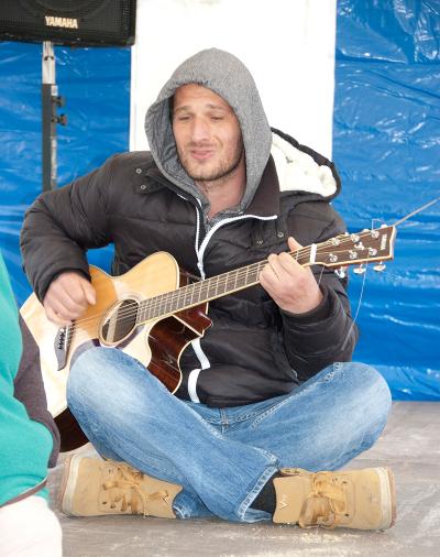 Sänger im Schneidersitz mit Gitarre