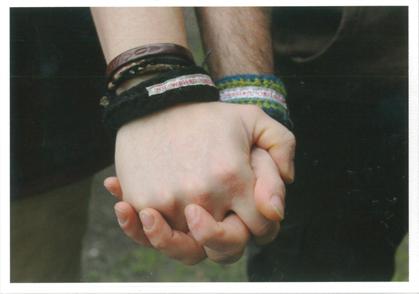"""Zwei ineinander gefaltete Männerhände, an deren Handgeleken Strick-Armbänder mit der Aufschrift """"wir-wollen-vielfalt.de"""" zu sehen sind."""