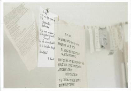 Wäscheleine mit Papier- und Textilblättern, die mit schwarzen Buchstaben, Worten und Sätzen bedruckt sind.