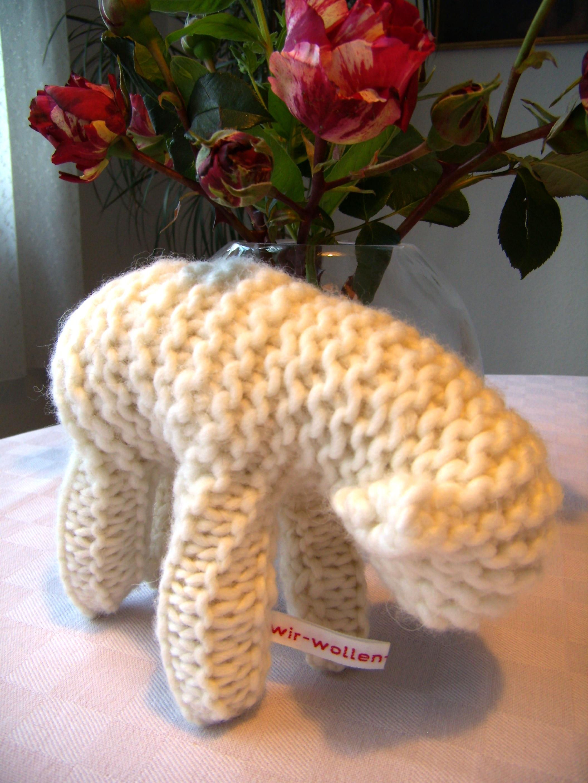 """Gestricktes Lamm aus weißer Wolle mit Wäschebändchen """"Wir wollen Vielfalt"""" vor einer Vase mit roten Rosen."""
