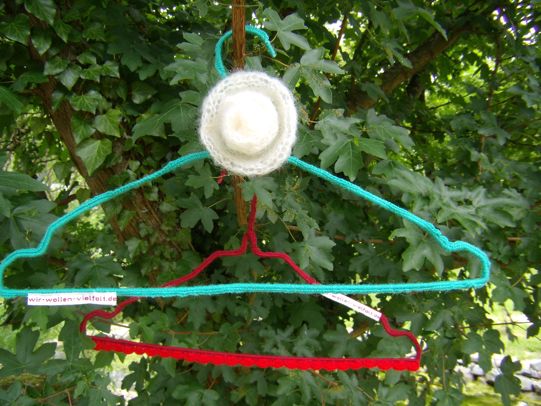 """Zwei Draht-Kleiderbügel mit der Aufschift """"wir-wollen-vielfalt.de"""", der eine rot, der andere grün umhäkelt, hängen in einem Busch voller Laub."""