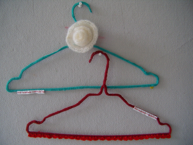"""Zwei Draht-Kleiderbügel mit der Aufschift """"wir-wollen-vielfalt.de"""", der eine rot, der andere grün umhäkelt, hängen an einer hellgrauen Pinwand."""