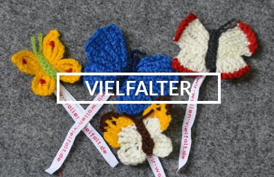 """Vier gehäkelte Schmetterlinge mit Bändern, auf denen """"wir-wollen-vielfalt.de"""" steht, in der Mitte das Wort """"Vielfalter""""."""