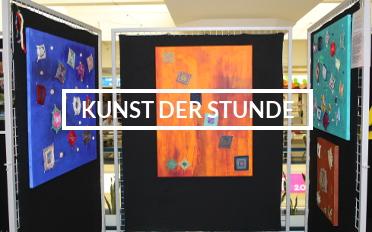 """Drei Stellwände mit abstrakten Bildern, in der Mitte die Aufschrift """"Kunst der Stunde""""."""