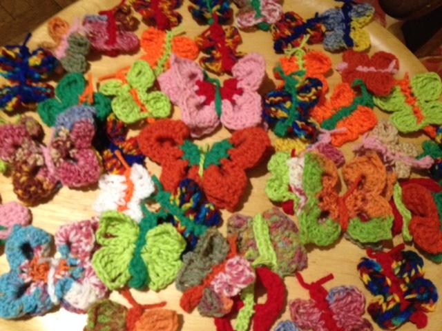 Runde Tischplatte mit verschiedenfarbigen Häkel-Schmetterlingen bedeckt.