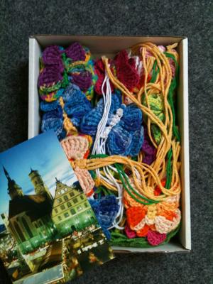 Einoffener Karton mit Häkel-Schmetterlingen und einer Stuttgart-Ansichtskarte.