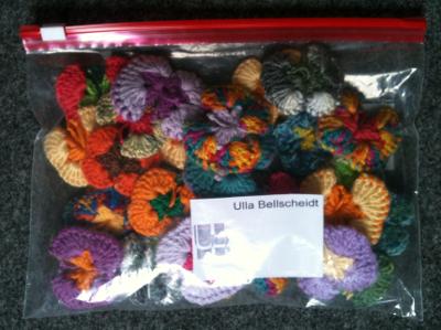 """Durchsichtiger Plastkbeutel mit gehäkelten Schmetterlingen und einer weißen Karte mit der Aufschrift """"Ulla Bellscheidt""""."""
