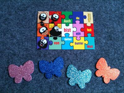 """Vier Moosgummi-Schmetterlinge und eine Postkarte mit der Aufschrift: """"Auch du bist ein Teil von Gottes bunter Welt."""""""