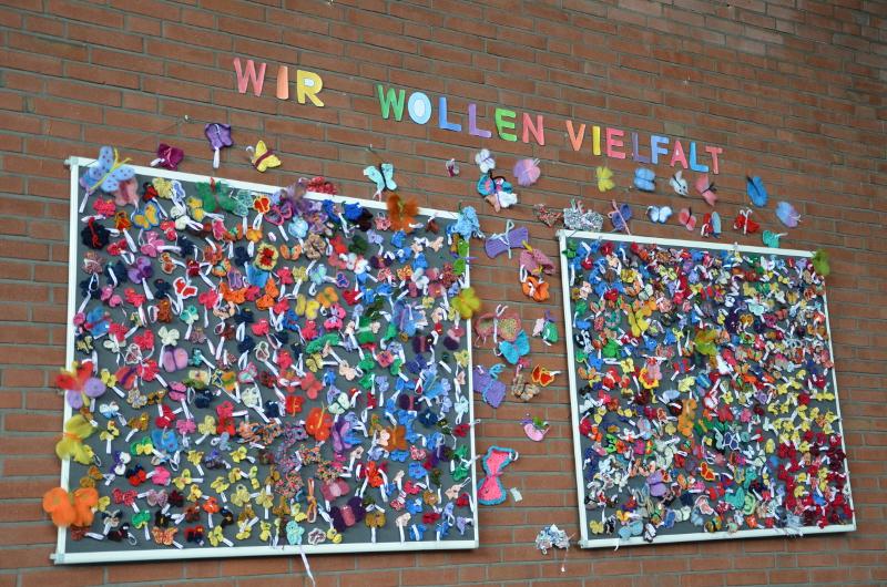 """Ziegelwand mit zwei Pinwänden voller Vielfalter, darüber in Papierbuchstaben die Worte: """"Wir wollen Vielfalt""""."""