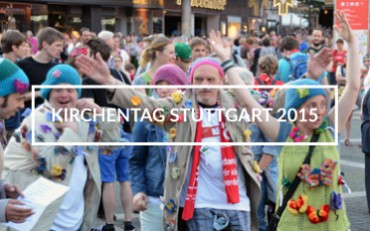 """Bunte Menschenmenge. In der Mitte des Bildes steht """"Kirchentag Stuttgart 2015""""."""