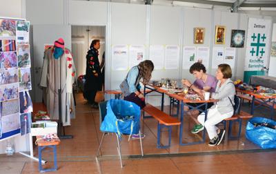 Kirchentags-Besucher am Tisch von Wir wollen Vielfalt im Zentrum Kirchentag Barrierefrei.