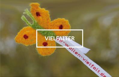 """Gelber Häkel-Schmetterling mit grünem Körper und Wäscheband mit Aufschrift """"wir-wollen-vielfalt.de"""". In der Mitte des Bildes steht das Wort """"Vielfalter""""."""