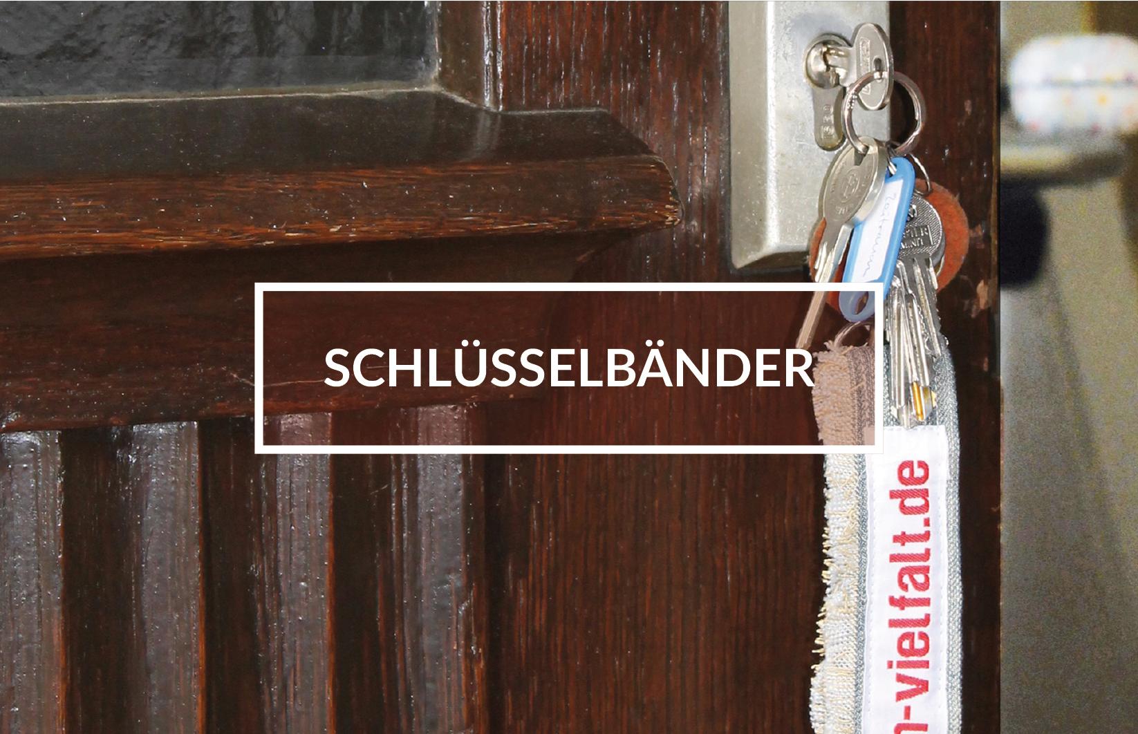 """Geöffnete Tür mit Schlüssel im Schloss, Schlüsselband mit der Aufschrift:""""vielfalt.de"""". In der Mitte des Bildes weiß gerahmter Kasten mit dem Schriftzug: """"Schlüsselbänder""""."""