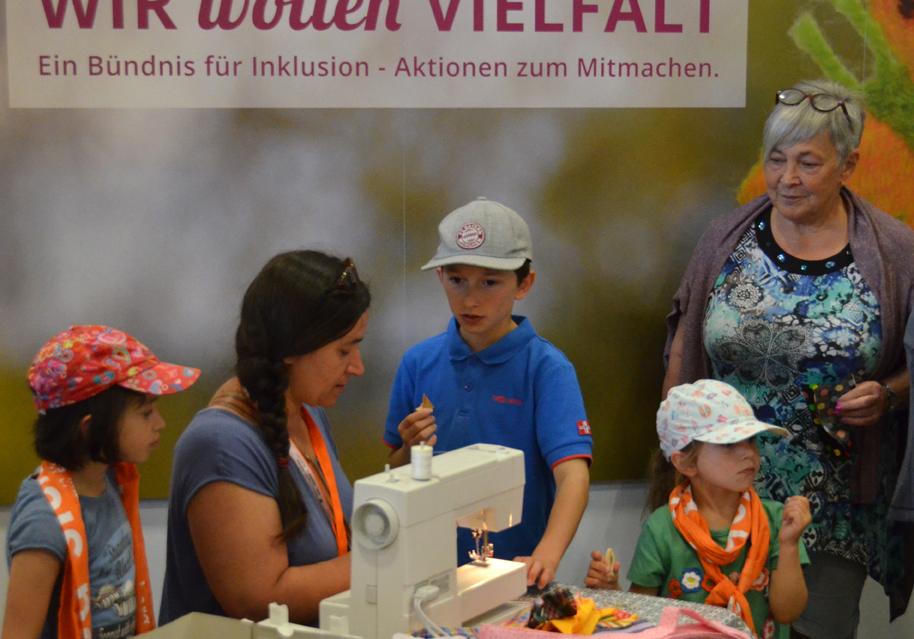 """Drei Generationen (zwei Frauen und drei Kinder) an der Nähmaschine von """"Wir wollen Vielfalt""""."""