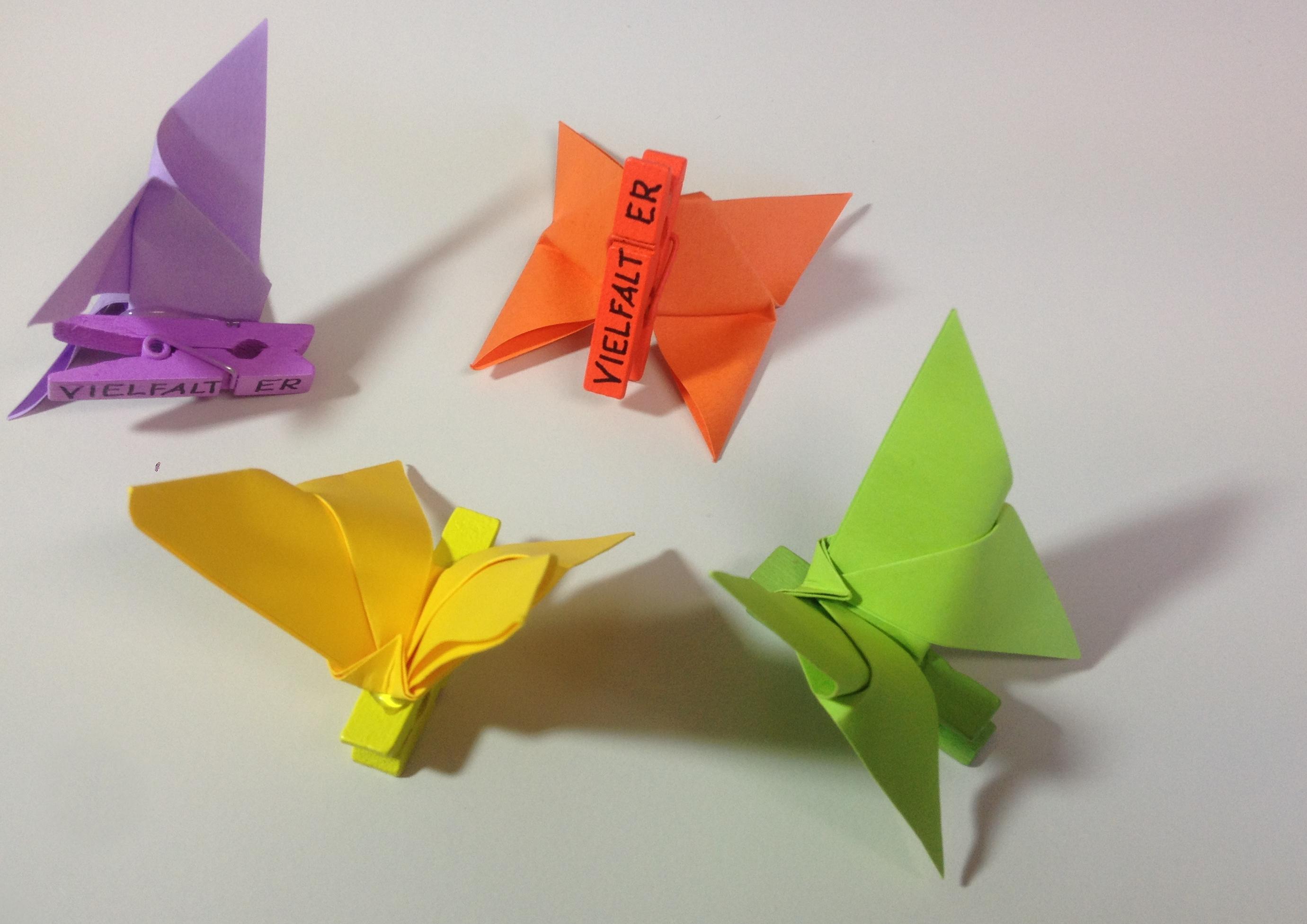 """Vier Schmetterlinge aus gefaltetem Papier und einer Serviettenklammer mit der Aufschrift """"Vielfalter"""""""
